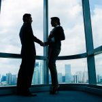 Asian business people handshake to seal deal in front of city skyline